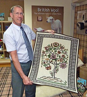 Timothy Booth holding a Carpets of Caring tapestry.